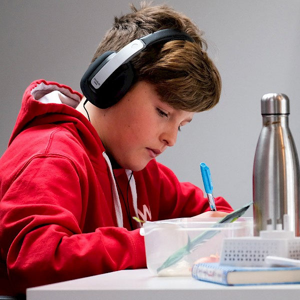 Student wearing headphones writing in front of laptop