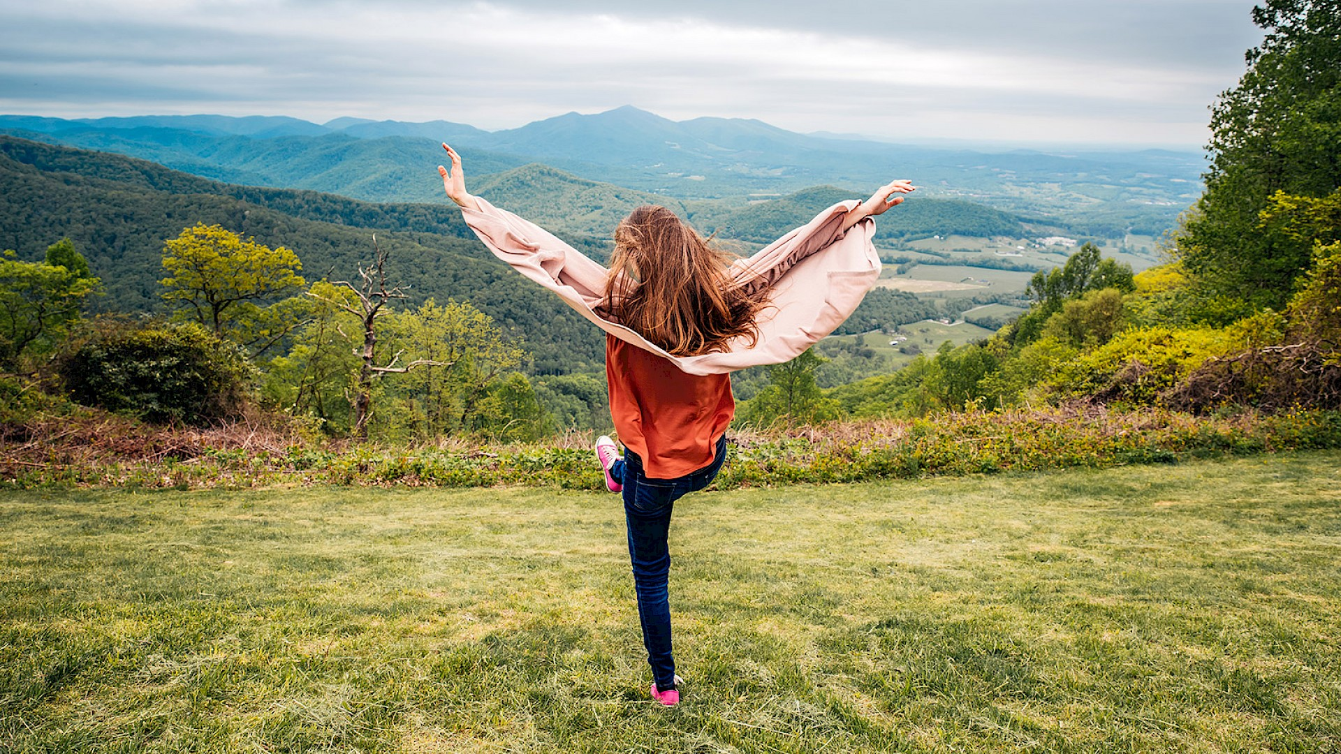 Teenage girl on top of a hill with her hands in the air