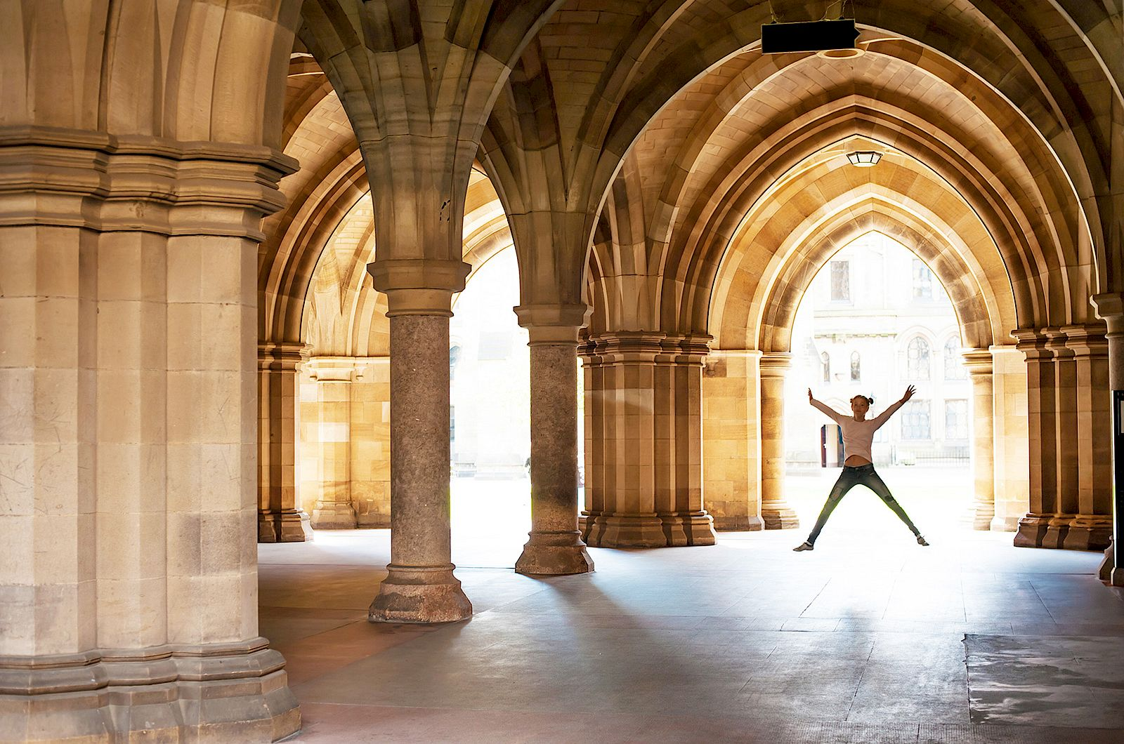 ISSFT student doing a star jump at the Undercroft, Glasgow University